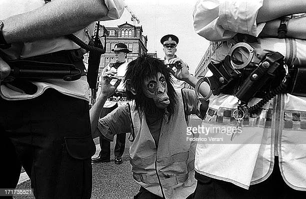 Man dressed as a monkey taunts police during the protests against G8 summit