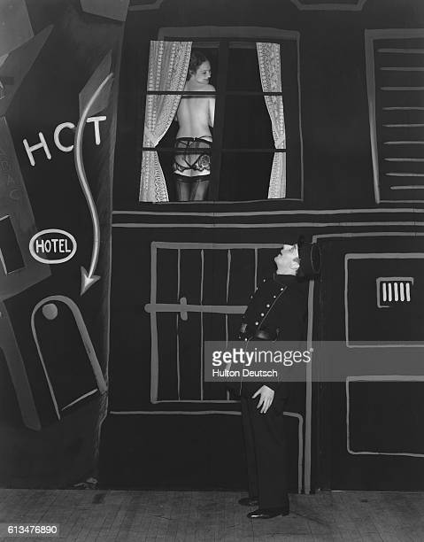 A man dressed as a police officer looks salaciously at a scantilyclad woman though a window in a theatrical backdrop during the Sparks Ballet's...