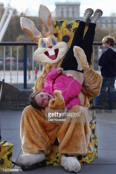 A man dressed as a rabbit holds a girl upside down on the South Bank on April 11 2012 in London England The South Bank which runs alongside the River...