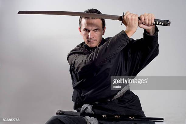 Man dressed as a samurai holding katana in the air