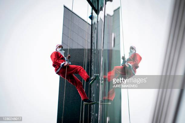Man dressed as a Santa Claus descends from the roof of the paediatric clinic in Ljubljana, Slovenia on December 21, 2020.