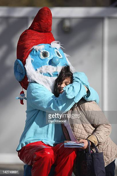 A man dressed as a smurf squeezes a girl on the South Bank on April 11 2012 in London England The South Bank which runs alongside the River Thames is...