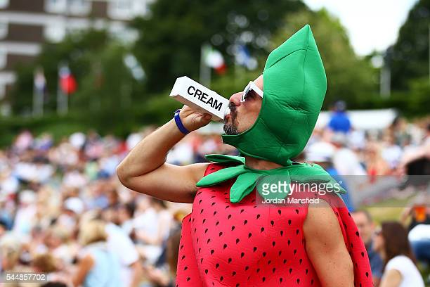 A man dressed as a strawberry drinks cream on Murray mound on day seven of the Wimbledon Lawn Tennis Championships at the All England Lawn Tennis and...