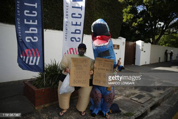 A man dressed as a sumo wrestler and a man dressed as a Trex dinosaur hold placards outside the Newlands stadium while trying to get tickets to the...