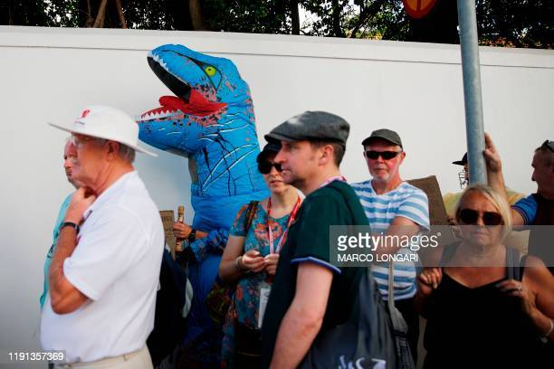 A man dressed as a Trex dinosaur holds a placard outside the Newlands stadium while trying to get tickets to the cricket game that is sold out before...