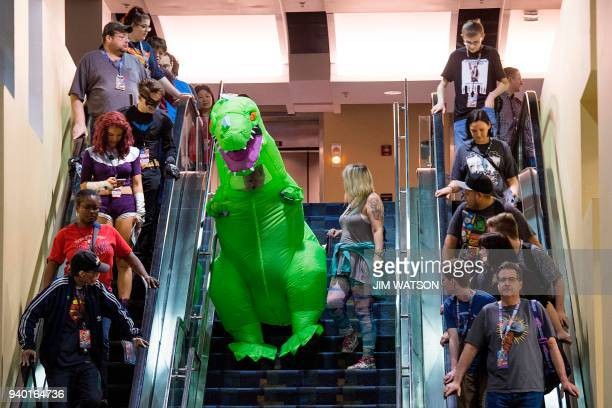 TOPSHOT A man dressed as a TRex tries to walk down the stairs as he attends Awesome Con in Washington DC on March 30 2018 Awesome Con is Washington...