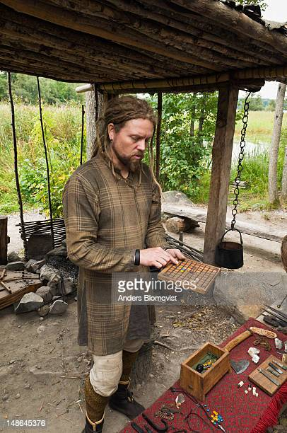 Man dressed as a Viking showing an ancient boardgame at Birka reconstructed Viking village.
