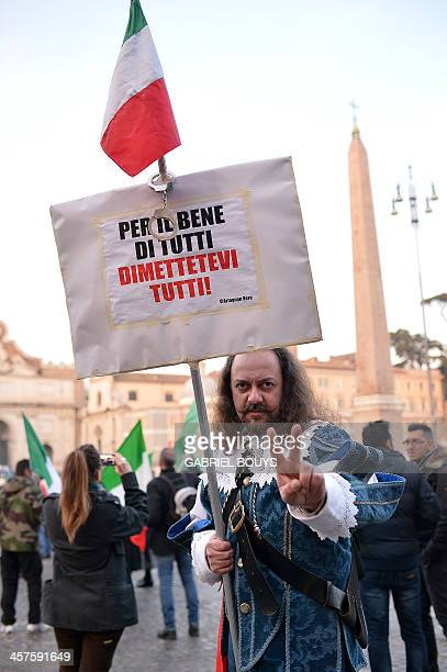 """Man dressed as an Alexandre Dumas' character D'Artagnan poses with a placard reading """"For the good of everybody, resign all"""" during a demonstration..."""