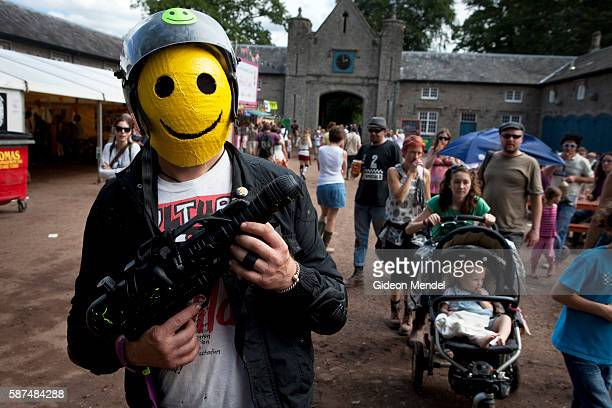 A man dressed as an armed yellow smiley face at the the Green Man festival This is an independent music festival held annually in a stunning natural...