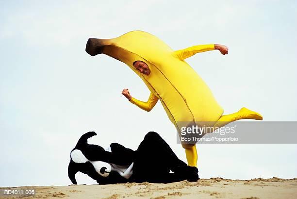 Man dressed as banana kicking man dressed as dog lying on ground
