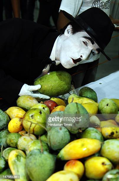 A man dressed as Charlie Champlin looking at Mangoes at Mango Festival at Dilli Haat Pitampure on July 6 2012 in New Delhi India