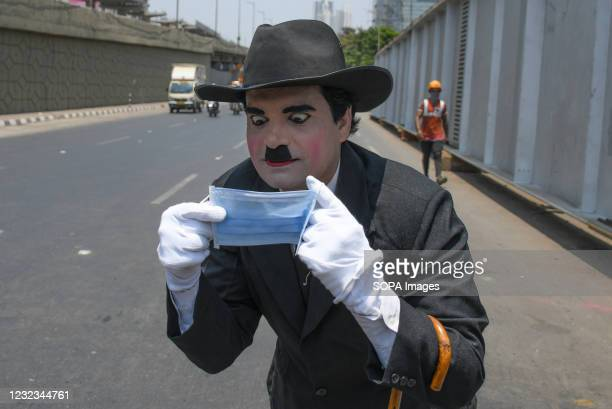 Man dressed as Charlie Chaplin creates awareness about wearing facemask in Mumbai. The covid-19 awareness drive to wish Charlie Chaplin a happy...