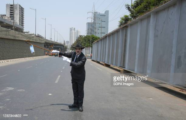 Man dressed as Charlie Chaplin hangs a facemask on a stick to create awareness about coronavirus disease in Mumbai. The covid-19 awareness drive to...