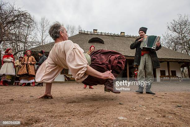 Man dressed as cossack performs traditional dance 'hopak' during Maslenitsa celebration in Mamayeva Sloboda Kyiv Ukraine on March 13 2016