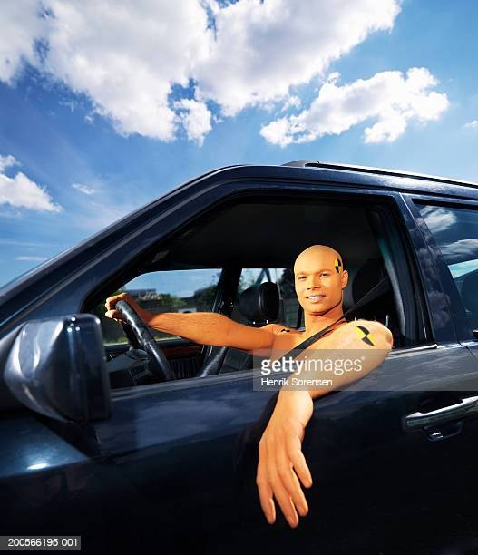Man dressed as crash test dummy sitting in car, portrait
