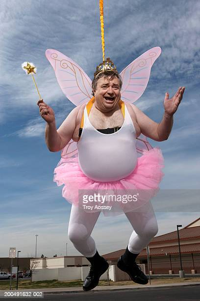 Man dressed as fairy, hanging in air, portrait