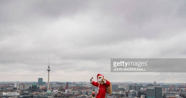 TOPSHOT A man dressed as Father Christmas aka Santa Claus poses on the top of the Kollhoff tower in front of a Berlin skyline on December 17 2017 as...