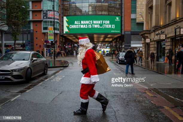 Man dressed as Father Christmas walks past COVID-19 signage displayed on the Arndale in the city centre as Manchester enters Tier 3 on December 02,...