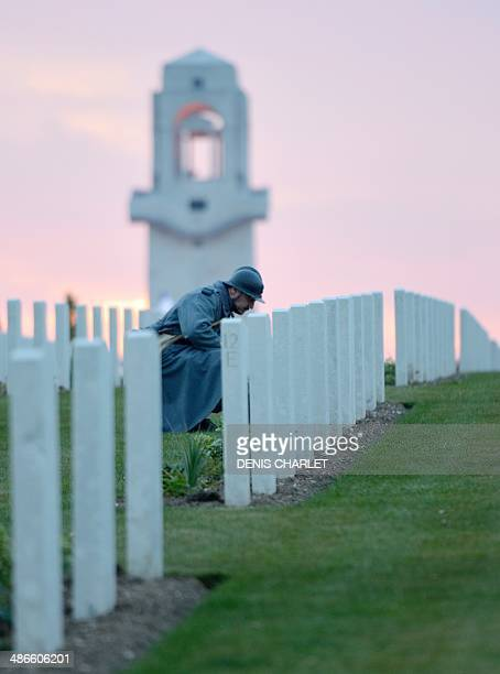 A man dressed as French soldier of the First World War looks at names on graves during a dawn service at the Australian War Memorial in the northern...