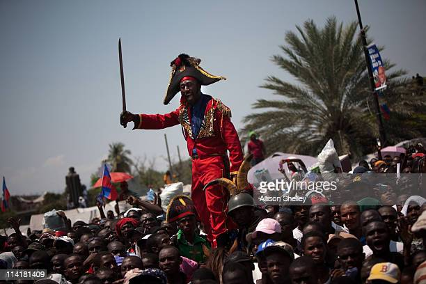 A man dressed as JeanJacques Dessalines the leader of the Haitian revolution stands outside of the fence around the Haitian presidential palace to...