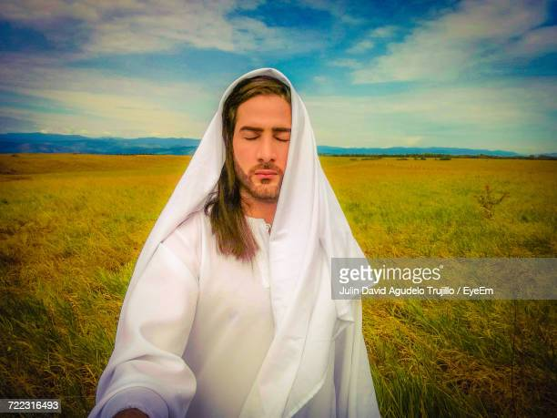 man dressed as jesus standing on grassy field against sky - jesus christ photos stock pictures, royalty-free photos & images