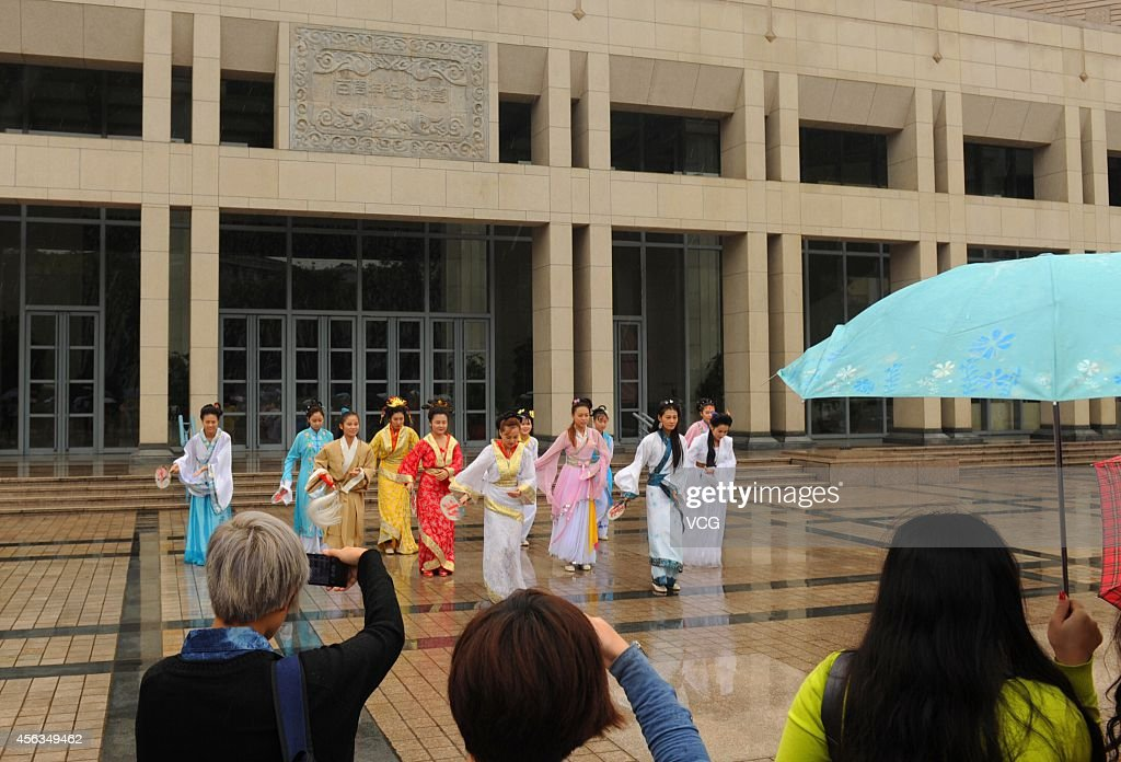 A man dressed as Jia Baoyu and twelve women dressed as Twelve Beauties of Jinling, main characters in the book of The Dream of Red Mansions dance 'Little Apple', a widespread internet meme by Chopstick Brothers, in front of the Peking University Hall on September 23, 2014 in Beijing, China. 'Jia Baoyu' and 'Twelve Beauties of Jinling' dance 'Little Apple' to welcome the upcoming 5th Cao Xueqin Art Festival on September 27 in Beijing. Cao Xueqin, author of The Dream of Red Mansions has been a traditional culture of China.