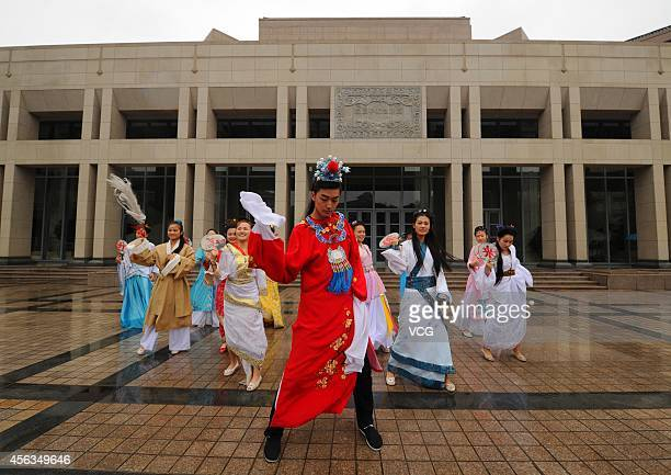 A man dressed as Jia Baoyu and twelve women dressed as Twelve Beauties of Jinling main characters in the book of The Dream of Red Mansions dance...