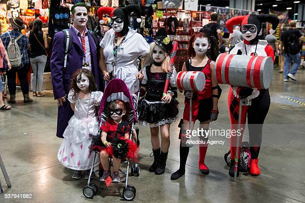 A man dressed as Joker poses for a photo with his family who are all dressed as Harley Quinns at Awesome Con which is being held at the Washington...