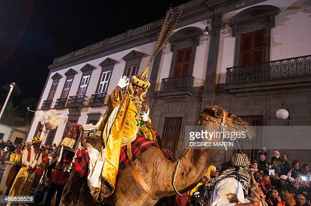 A man dressed as King Balthazar one the three wise men or Kings rides a camel during the Three Wise Men Parade in Tenerife on the Spanish Canary...