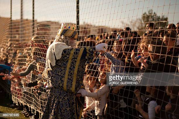 A man dressed as King Melchior meets children upon his arrival with men dressed as Kings Balthazar and Caspar otherwise known as the three wise men...