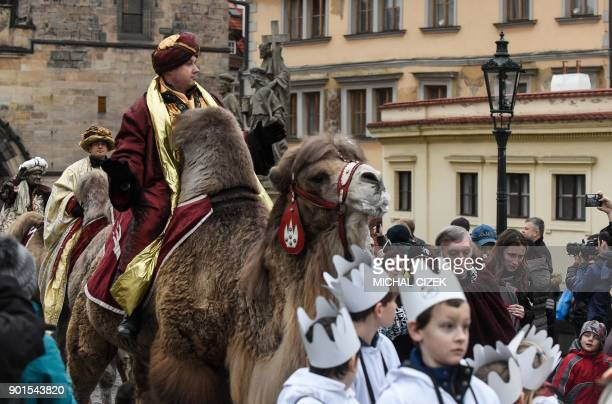 A man dressed as one of the Three King rides a camel accros the Charles Bridge as he takes part in a procession markng the kings' journey to Jesus...