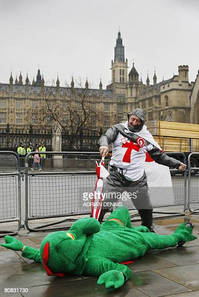 A man dressed as Saint George pretends to spear a dragon with an umbrella outside the Houses of Parliament in London on April 23 2008 The act was...