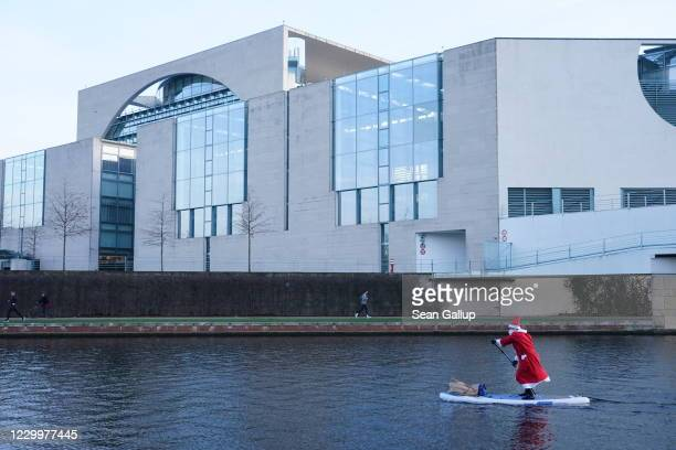 Man dressed as Saint Nicholas paddle boards on the Spree River in Berlin next to the Chancellery on December 6, 2020 in Berlin, Germany. Authorities...