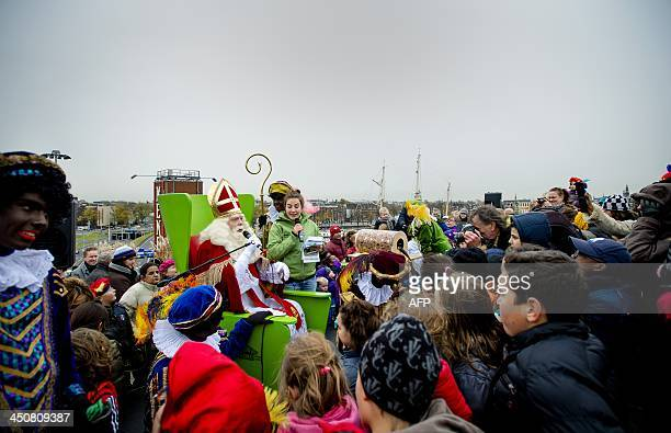 A man dressed as Saint Nicholas talks to children next to his sidekick Black Pete on the roof of the NEMO technology Museum in Amsterdam on November...
