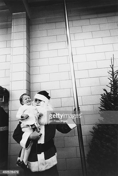 A man dressed as Santa Claus carries a young girl to the fireman's pole in a firehouse New York City circa 1973