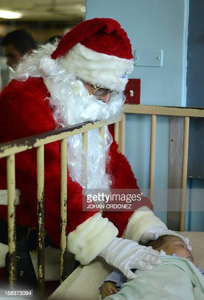 A man dressed as Santa Claus cheers a little patient in the pediatric yard of the San Juan de Dios Hospital on December 14 2012 in Guatemala City AFP...