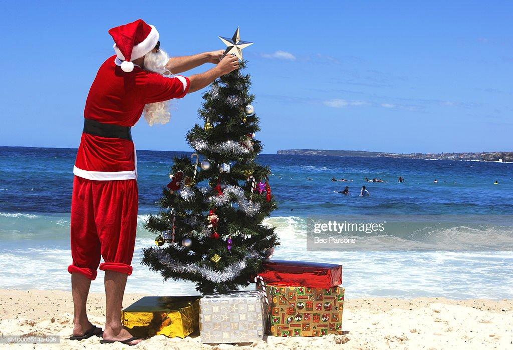 man dressed as santa claus decorating christmas tree on beach rear view stock photo - Christmas Tree Santa