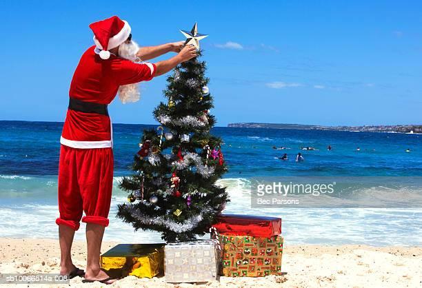 Man dressed as Santa Claus decorating christmas tree on beach, rear view