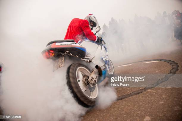 Man dressed as Santa Claus does a burnout with his motorcycle before Christmas ride on December 19, 2020 in Sofia, Bulgaria. The Christmas Ride is an...