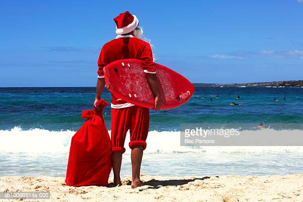 Man dressed as Santa Claus holding sack and surf board standing on beach, rear view