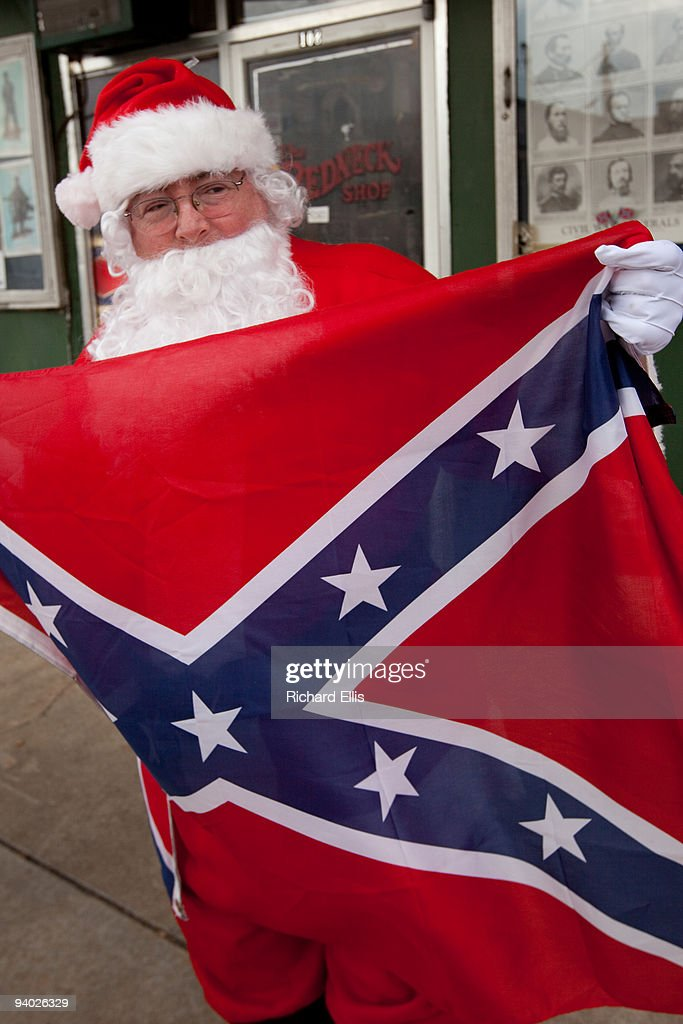 A man dressed as Santa Claus holds a Confederate flag during a white-supremacist event outside the Redneck Shop December 5, 2009 in Laurens, South Carolina. The American Nazi Party & International Knights of the Ku Klux Klan held their 7th annual White Unity Christmas Party which was publicized as a family event.