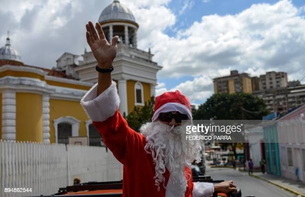 """Man dressed as Santa Claus is seen during the event """"Santa en las calles"""" in the Pastora shantytown in Caracas on December 16, 2017. Santa in the..."""