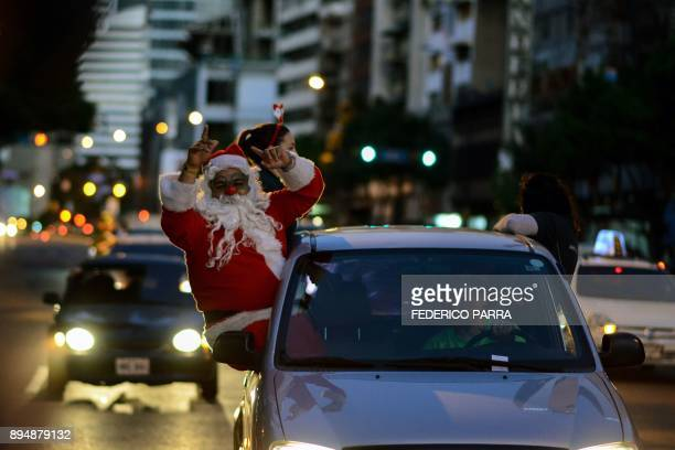 """Man dressed as Santa Claus is seen during the event """"Santa en las calles"""" in the streets of Caracas on December 16, 2017. """"Santa in the Streets"""" is a..."""