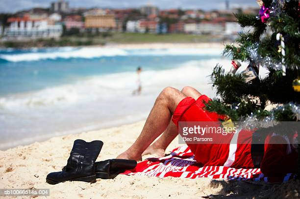 Man dressed as Santa Claus lying behind christmas tree on beach, low section
