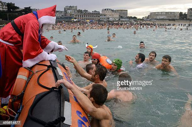 A man dressed as Santa Claus offers chocolates to people enjoying their last sea bath of the year on December 31 2013 in Dinard western France AFP...