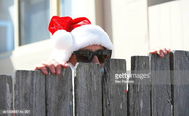 Man dressed as Santa Claus peeking from behind wooden fence, close up