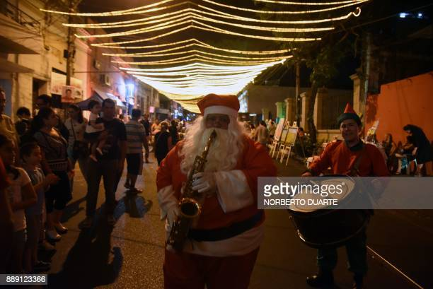 A man dressed as Santa Claus performs during in the inauguration of one of the streets of Asuncion decorated with Christmas on December 9 2017 / AFP...