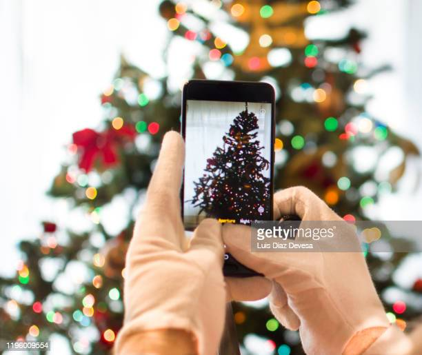man dressed as santa claus photographing the christmas tree - 2020 2029 stock pictures, royalty-free photos & images