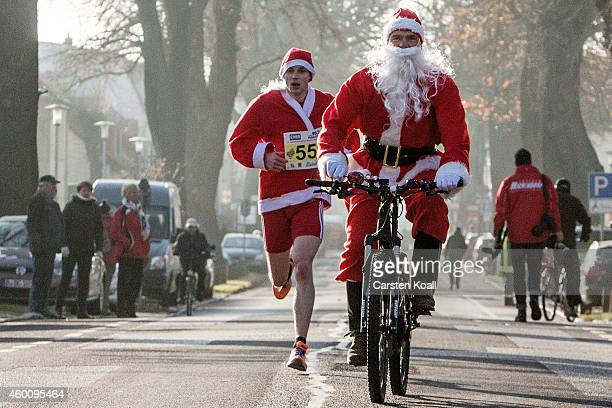 A man dressed as Santa Claus rides a bicycle as he and other participants dressed as Santa Claus attend the annual Santa Run on December 7 2014 in...