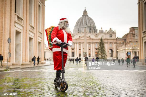 Man dressed as Santa Claus rides a electric scooter around St. Peter's Square on December 08, 2020 in Rome, Italy. While decorations go up to...